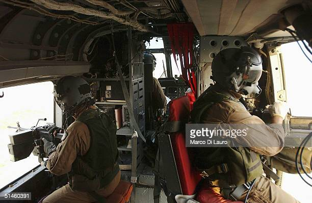 Two Italian Air Force gunners from the Italian Joint Task Force Iraq, 6? ROA sit poised with their machine guns as they fly on a HH-3F helicopter...
