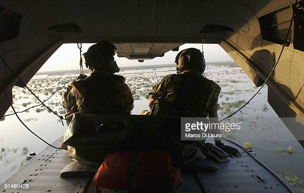 Two Italian Air Force gunners from the Italian Joint Task Force Iraq, 6? ROA, sit poised with their machine guns as they fly on a HH-3F helicopter...
