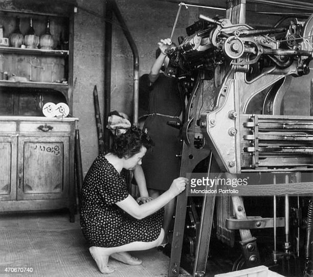 Two Italian women working wool on a loom at home Biella 1964