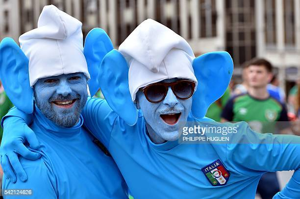 TOPSHOT Two Italy's supporters dressed as smurfs cartoon character pose as they gather with other football fans in the streets of Lille on June 22...