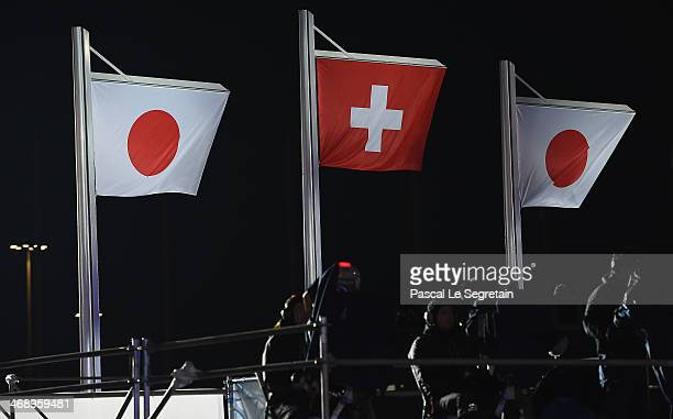 Two Japanese and a Swiss flag are raised for silver medalist Ayumu Hirano of Japan gold medalist Iouri Podladtchikov of Switzerland and bronze...