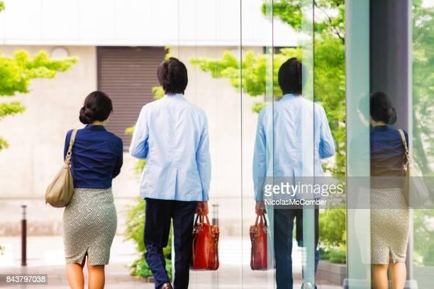 twee japanse bedrijfsmensen lopen naast elkaar achter bekijken - alleen volwassenen stockfoto's en -beelden