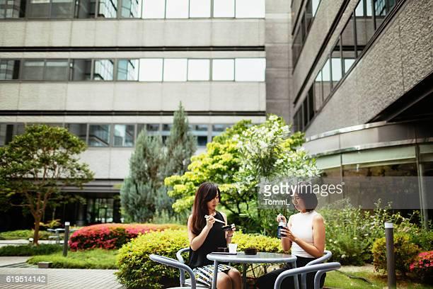 two japanese business women having lunch outdoor - 昼食 ストックフォトと画像