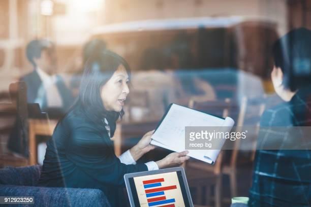 2 人の日本のビジネス女性がカフェでビジネスの話