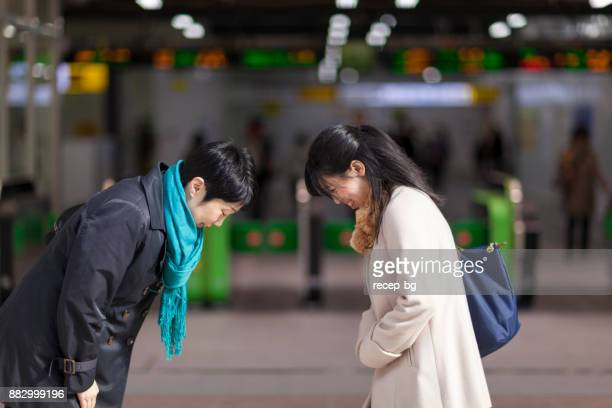 Two Japanese Businesswomen Bowing To Each Other At Station