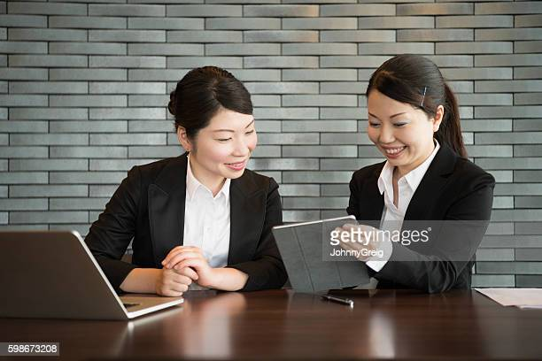 Two Japanese businesswomen using laptop and tablet