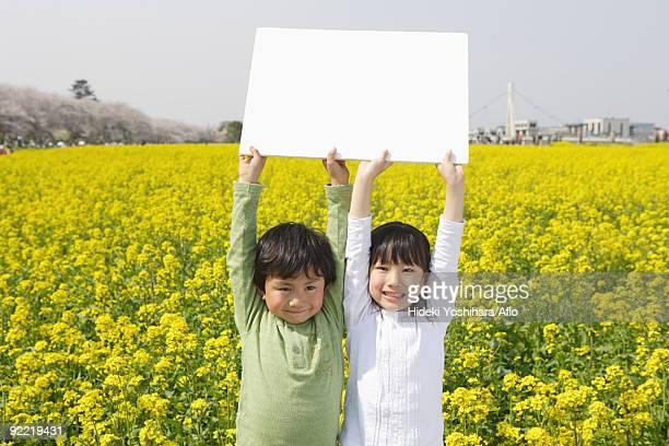 Two Japanese children holding white cardboard
