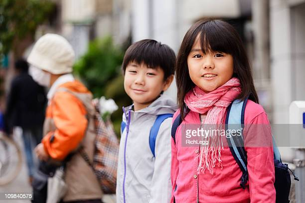 2 つの子供たちは、街の通りの上に立つ