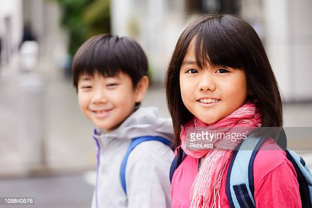 Two Japanese Children Standing on a City Street