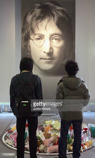 Two Japanese fans look at tributes laid in front of a giant photograph of John Lennon from at the John Lennon Museum on December 8 2004 in Saitama...