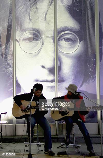 Two Japanese fans perform in front of a giant photograph of John Lennon at the John Lennon Museum on December 8 2004 in Saitama Japan Fans gathered...