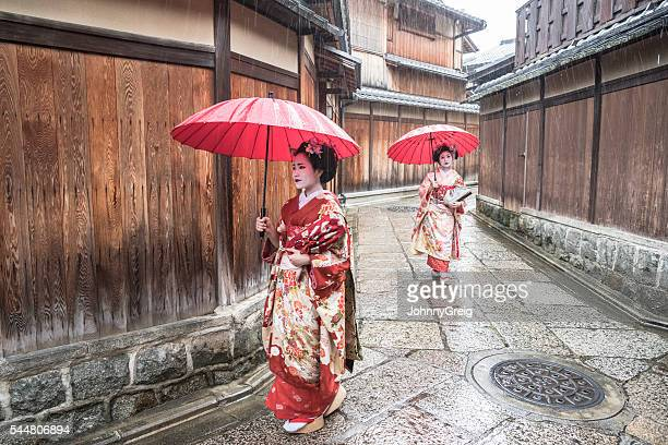 Two Japanese geishas in kimonos with red parasols