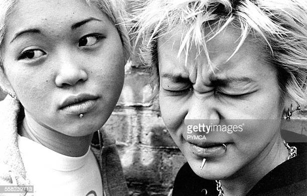 Two Japanese girls with facial piercings one screwing her face up UK 1990s