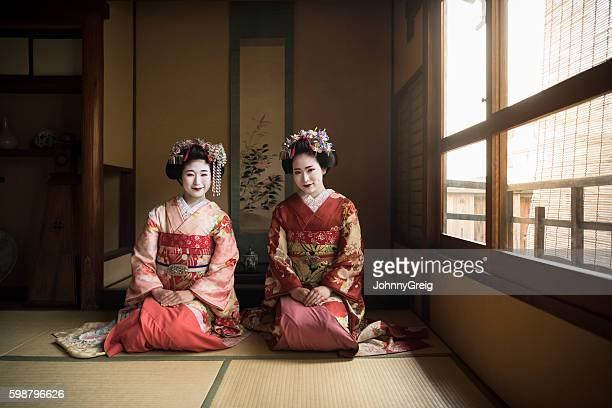 two japanese maiko kneeling on floor wearing kimonos - geisha stock pictures, royalty-free photos & images