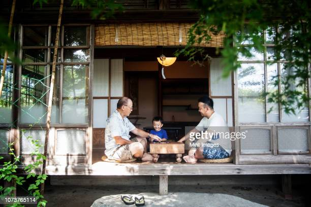 two japanese men and little boy sitting on floor on porch of traditional japanese house, playing go. - 祖父 ストックフォトと画像