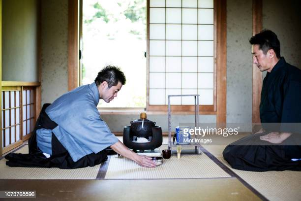 two japanese men wearing traditional kimonos kneeling on floor during tea ceremony. - ceremony stock pictures, royalty-free photos & images