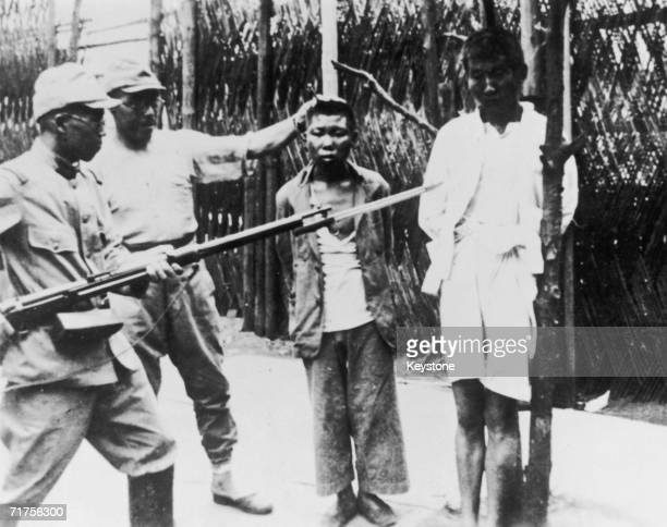 Two Japanese soldiers taunt a pair of young Chinese prisoners before their execution during the Second SinoJapanese War 22nd August 1938