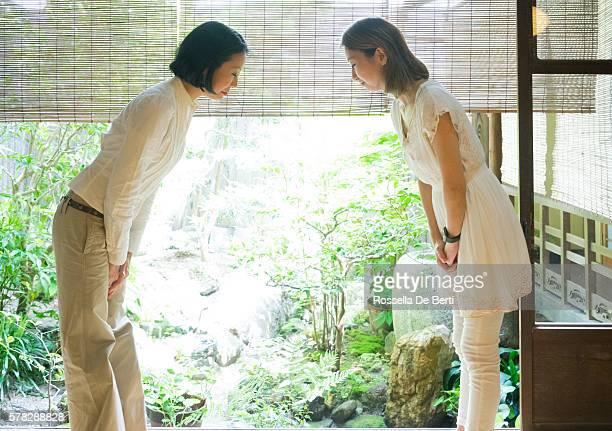 Two Japanese women bowing with respect in a traditional house