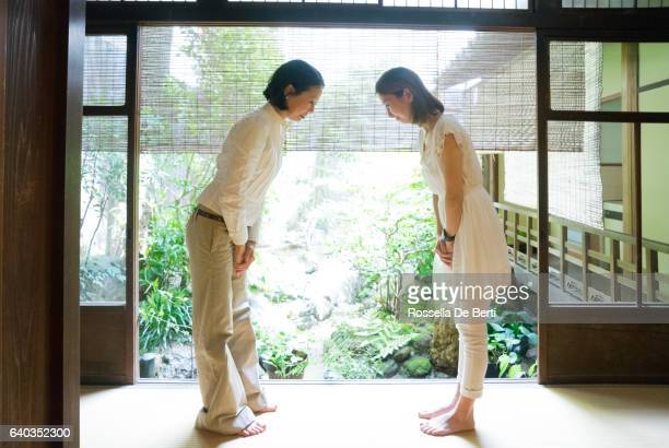 two japanese women bowing with respect in a traditional house - wabi sabi stock pictures, royalty-free photos & images
