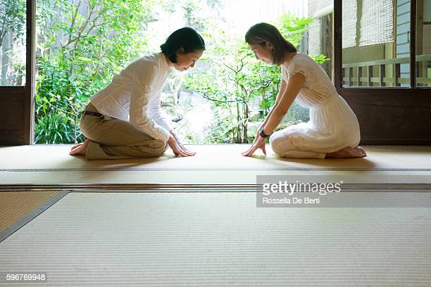 Two Japanese women bowing with respect