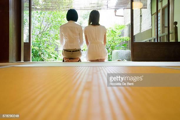 two japanese women contemplating the garden from the veranda - mulher orando de joelhos imagens e fotografias de stock