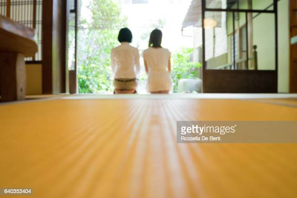 two japanese women contemplating the garden from the veranda - wabi sabi stock pictures, royalty-free photos & images