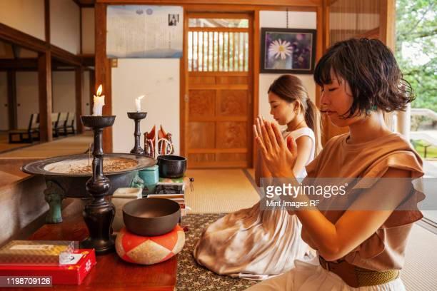 two japanese women kneeling in buddhist temple, praying. - travel ストックフォトと画像