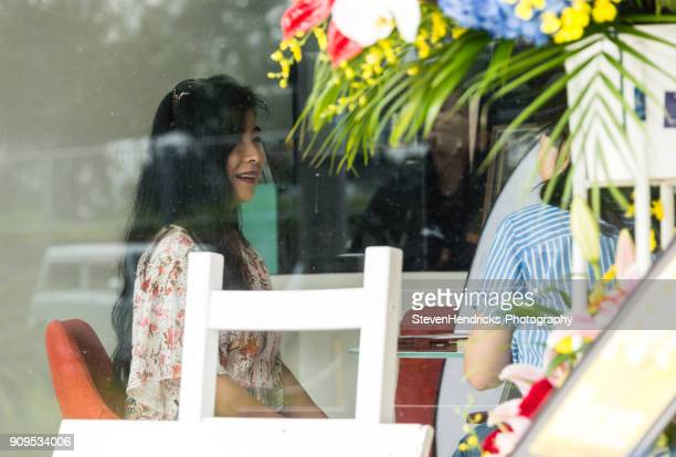 Two Japanese women laugh and talk in a Cafe