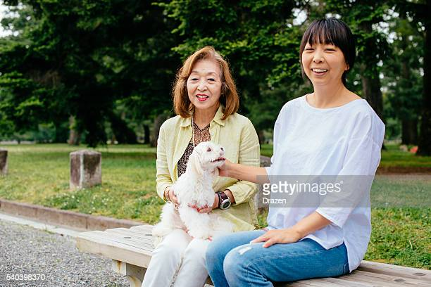 Two Japanese women, senior and mature, relaxing in park
