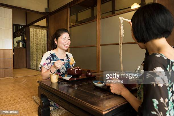 Two Japanese women sitting at table eating food