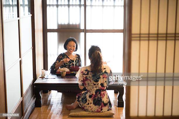 Two Japanese women sitting at table in restaurant
