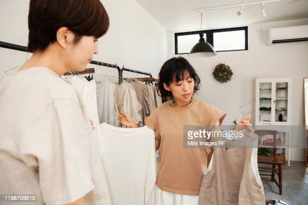 two japanese women standing in a small fashion boutique, looking at tops. - シンプルな暮らし ストックフォトと画像