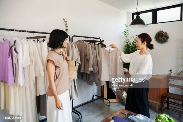 two japanese women standing in a small fashion boutique, looking at tops. - ファッションデザイナー ストックフォトと画像