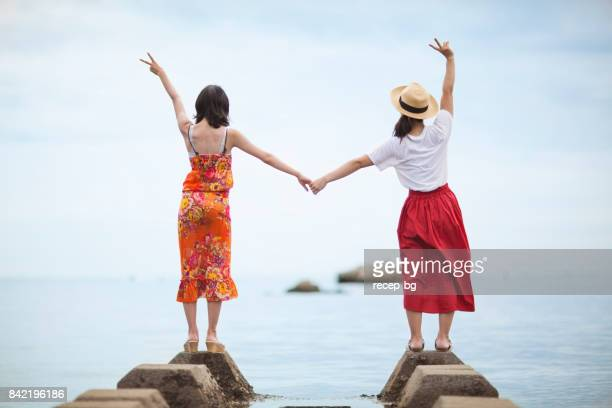 Two Japanese Women Standing Near The Sea