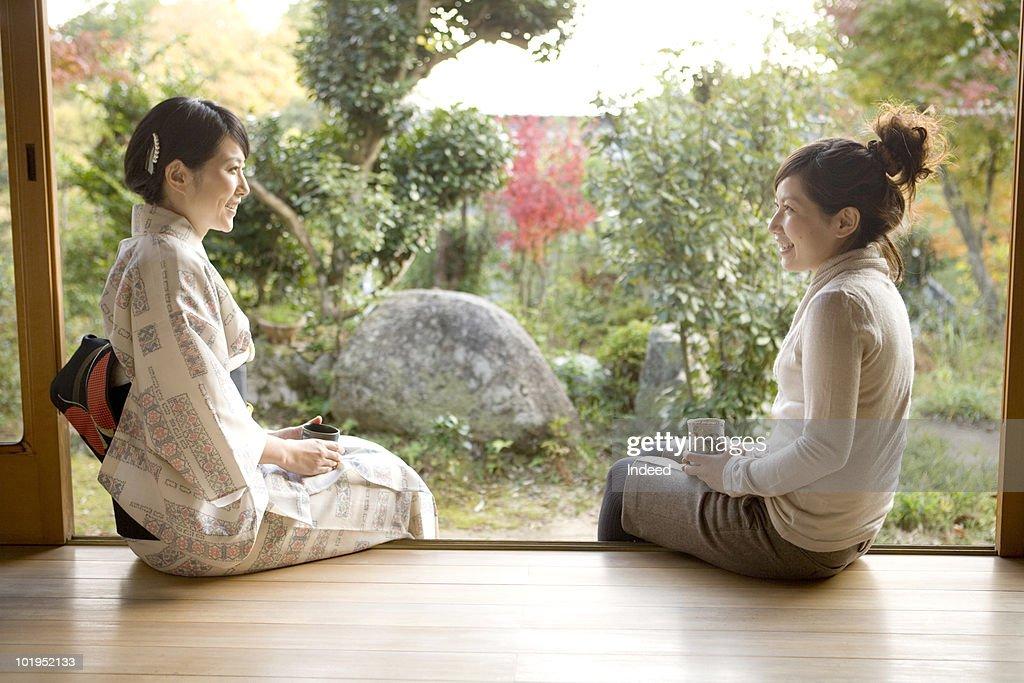 Two Japanese women talking on the veranda : Stock Photo