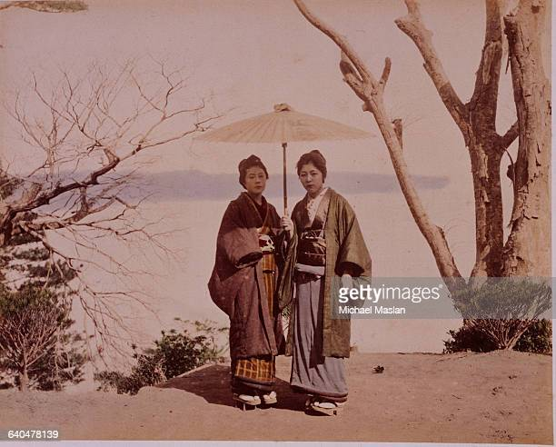 Two Japanese women wearing traditional clothing. One is holding a paper umbrella to shade them from the sun. Japan, ca. 1910s-1920s.