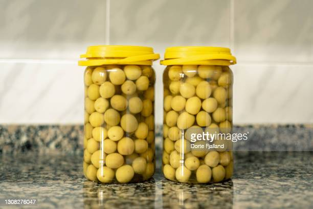 two jars of olives in brine on the kitchen counter - dorte fjalland stock pictures, royalty-free photos & images