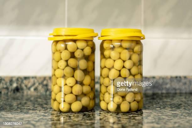 two jars of olives in brine on the kitchen counter - dorte fjalland fotografías e imágenes de stock