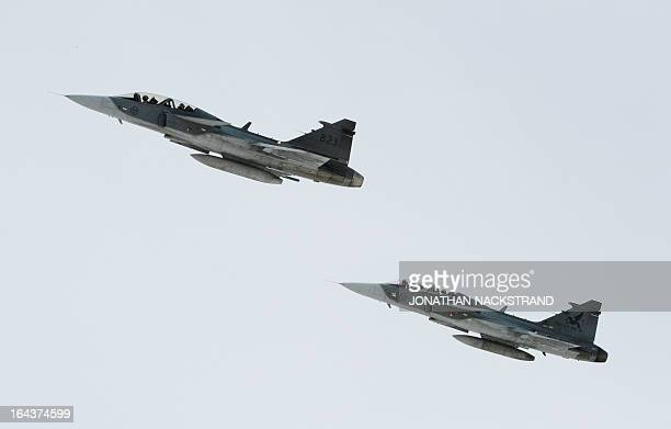 Two JAS 39 Gripen lightweight singleengine multirole fighters manufactured by the Swedish aerospace company Saab fly on March 23 2013 above the town...