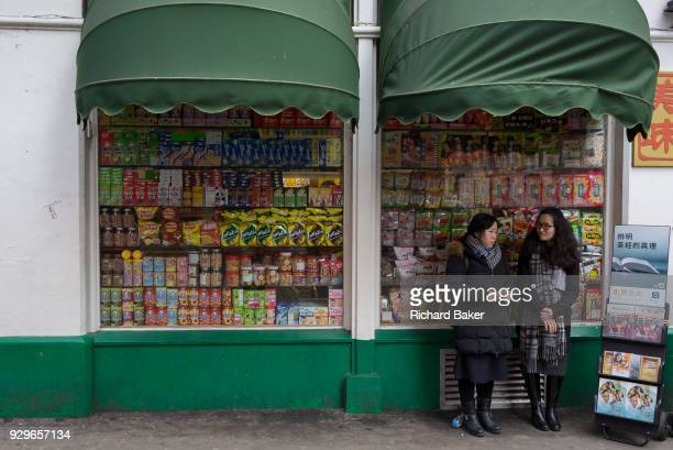Two Jehovah's Witnesses stand with copies of the Watchtower magazine next to a shop window of assorted snacks on shelves in a corner shop on Gerrard...