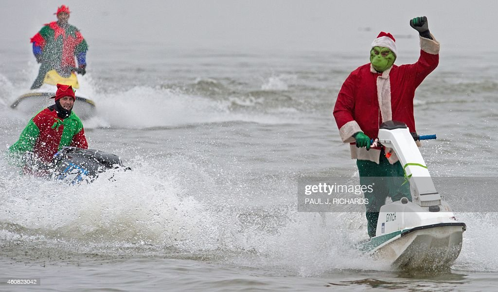 Two jet-skiing Elves (L) follow the Grinch along the Potomac River off Old Town Alexandria, Virginia, not far from Washington, DC December 24, 2014 during the annual water-skiing Santa event.