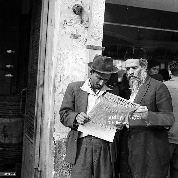 Two Jewish men reading a newspaper in a street in Israel