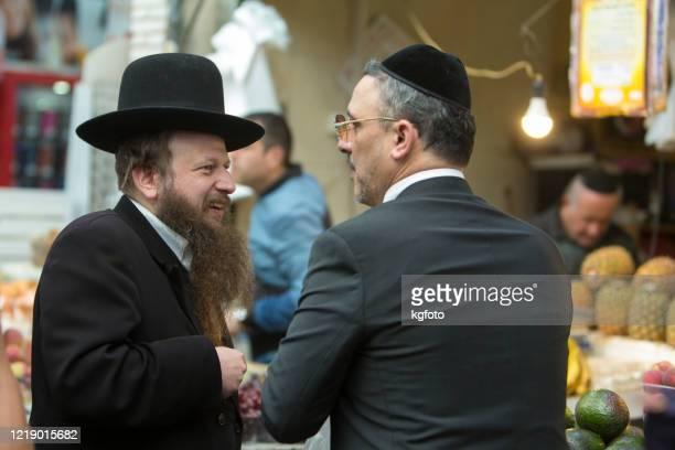 två judiska män med yarmulke och hatt pratar med varandra i mahane yehuda, den berömda marknaden i jerusalem gamla stan, israel - judendom bildbanksfoton och bilder