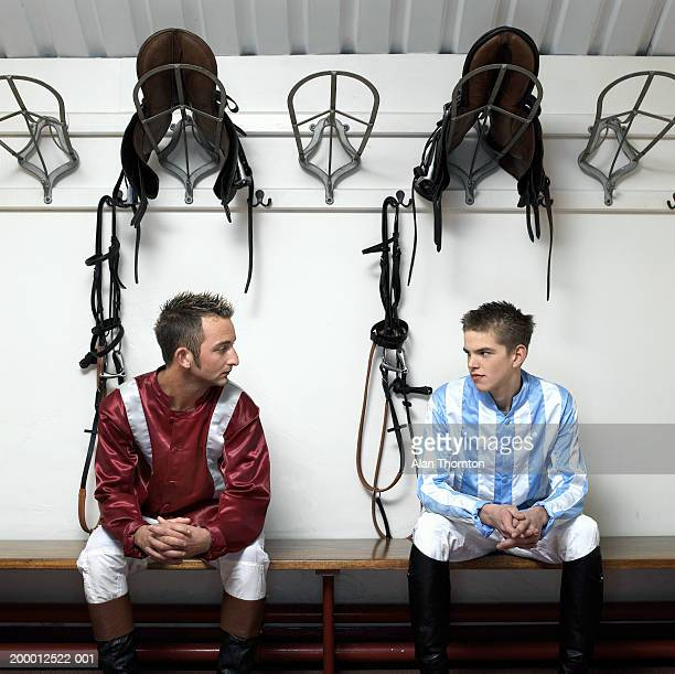 Two jockeys looking at each other under saddles on hooks