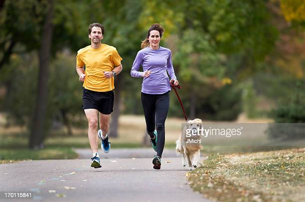 Two joggers and a golden retriever running on a paved trail