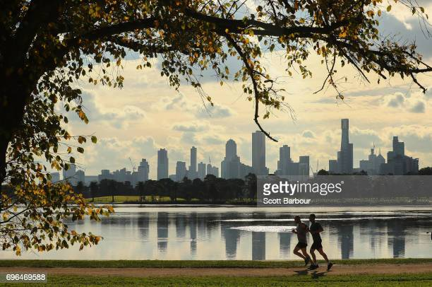 Two joggers run along Albert Park Lake on an Autumn day with highrise and apartment buildings in the city in the background on June 16 2017 in...