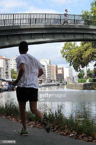 Two joggers run on August 27 on the banks of the Canal du Midi at the SaintSauveur port in Toulouse southwestern France AFP PHOTO REMY GABALDA