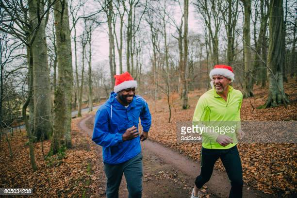 two joggers up the trails in the forest at christmas - santa hat stock photos and pictures