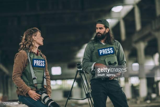 zwei journalisten im kriegsgebiet - reporterstil stock-fotos und bilder