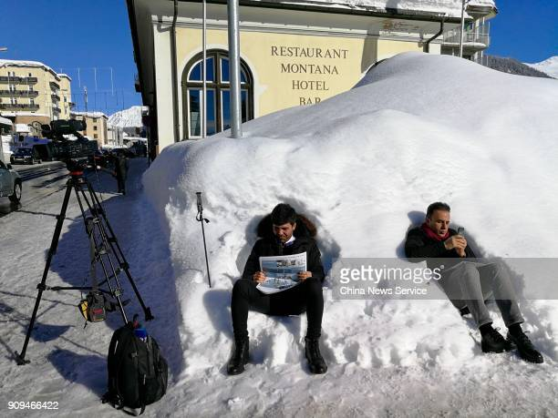 Two journalists rest on the snow on the opening day the World Economic Forum 2018 annual meeting on January 23 2018 in Davos Switzerland The World...